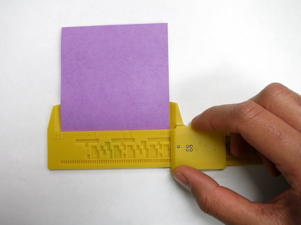 shows the 12-inch Braille Caliper being used to measure a piece of paper